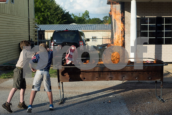 Landon Wilson, 11, and Lance Krieg, 8, throw a flag into the fire during a flag retirement ceremony at Cozad Insurance Group in Lindale, Texas, on Tuesday, July 11, 2017. Scouts and members of the community retired 90 flags in the ceremony. (Chelsea Purgahn/Tyler Morning Telegraph)