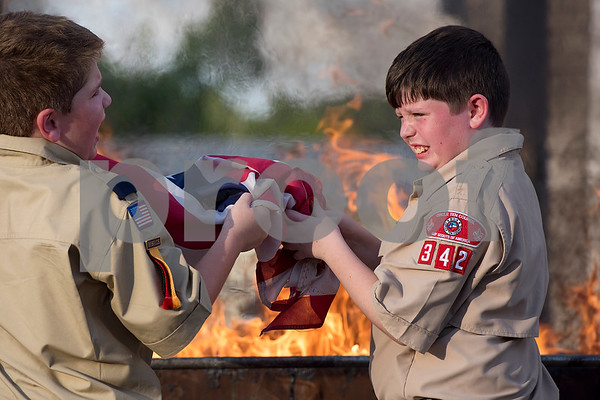 Wyatt Rounsavall, 10, right, reacts to the heat of the fire during a flag retirement ceremony at Cozad Insurance Group in Lindale, Texas, on Tuesday, July 11, 2017. Scouts and members of the community retired 90 flags in the ceremony. (Chelsea Purgahn/Tyler Morning Telegraph)