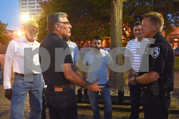Tyler Police Department Public Information Officer Don Martin, right, meets with members of the East Texas Islamic Society including Nabi Erikin, left, at the community vigil to encourage unity among citizens in East Texas hosted by the City of Tyler Thursday, July 14 at T.B. Butler Fountain Square in downtown Tyler.  (Sarah A. Miller/Tyler Morning Telegraph)