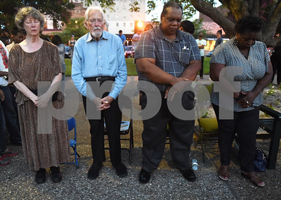 Ellen O'Brien, Max Lafser, Jeff Williams and Dorinda Williams close their eyes during a moment of silence at a community vigil to encourage unity among citizens in East Texas hosted by the City of Tyler Thursday, July 14 at T.B. Butler Fountain Square in downtown Tyler.  (Sarah A. Miller/Tyler Morning Telegraph)