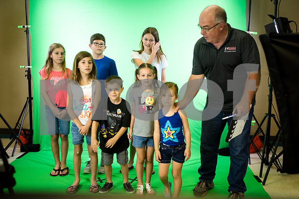 Richard Hall, right, helps children get ready for a green screen video during a Family Fun Day event hosted by the Tyler Morning Telegraph at Discovery Science Place in Tyler, Texas, on Tuesday, July 18, 2017. Kids received balloons and goody bags and had a chance to win prizes. (Chelsea Purgahn/Tyler Morning Telegraph)