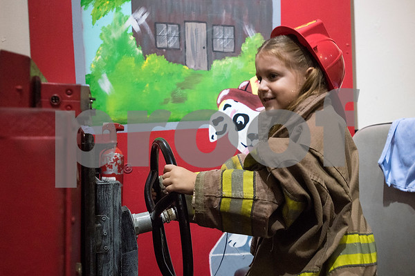 Laine Shumake, 6, plays dress up as a firefighter during a Family Fun Day event hosted by the Tyler Morning Telegraph at Discovery Science Place in Tyler, Texas, on Tuesday, July 18, 2017. Kids received balloons and goody bags and had a chance to win prizes. (Chelsea Purgahn/Tyler Morning Telegraph)
