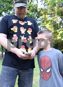 Barrett Owens, 7, of Lindale, watches his father Brian Owens play Pokemon Go at Southside Park in Tyler Tuesday July 19, 2016. After a Facebook event was posted, 300 people met at park and walked Rose Rudman Trail to play Pokemon Go Tuesday.   (Sarah A. Miller/Tyler Morning Telegraph)