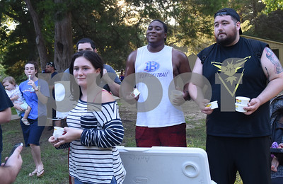 Aniekan Isong and Marc De La Garza hand out frozen custard from Andy's to people playing the Pokemon Go mobile game at Southside Park in Tyler Tuesday July 19, 2016. After a Facebook event was posted, 300 people met at park and walked Rose Rudman Trail to play Pokemon Go Tuesday.   (Sarah A. Miller/Tyler Morning Telegraph)
