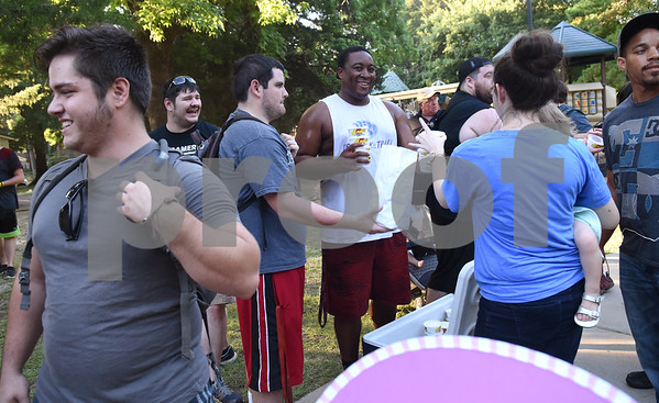Aniekan Isong, center, hands out frozen custard from Andy's to people playing the Pokemon Go mobile game at Southside Park in Tyler Tuesday July 19, 2016. After a Facebook event was posted, 300 people met at park and walked Rose Rudman Trail to play Pokemon Go Tuesday.   (Sarah A. Miller/Tyler Morning Telegraph)