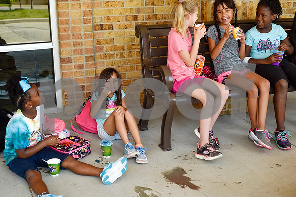 From left to right, Keara Johnson, 8, Mia Lemus, 7, Mackenzie Davis, 9, Isabella Martinez, 10 and Aleesia Turner, 9, sit and eat snow cones during Rose City Summer Camps at Dixie Elementary School in Tyler, Texas, on Wednesday, July 19, 2017. Rose City Summer Camps, a ministry of The Mentoring Alliance, is a faith-based and academic summer camp for kids. (Chelsea Purgahn/Tyler Morning Telegraph)