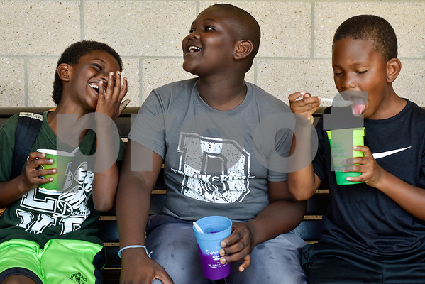 Christion Taylor, 7, laughs while Tristen Taylor, 9, talks and Peyton Brown, 7, eats a snow cone during Rose City Summer Camps at Dixie Elementary School in Tyler, Texas, on Wednesday, July 19, 2017. Rose City Summer Camps, a ministry of The Mentoring Alliance, is a faith-based and academic summer camp for kids. (Chelsea Purgahn/Tyler Morning Telegraph)