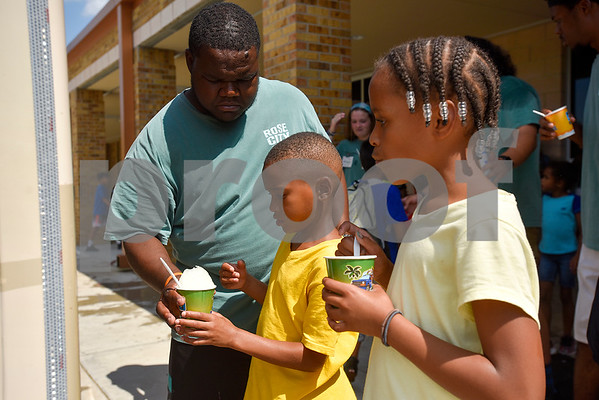 Xavier Elliott hands a snow cone to Kingston Austin, 7, while his sister Francesca, 9, eats her snow cone during Rose City Summer Camps at Dixie Elementary School in Tyler, Texas, on Wednesday, July 19, 2017. Rose City Summer Camps, a ministry of The Mentoring Alliance, is a faith-based and academic summer camp for kids. (Chelsea Purgahn/Tyler Morning Telegraph)