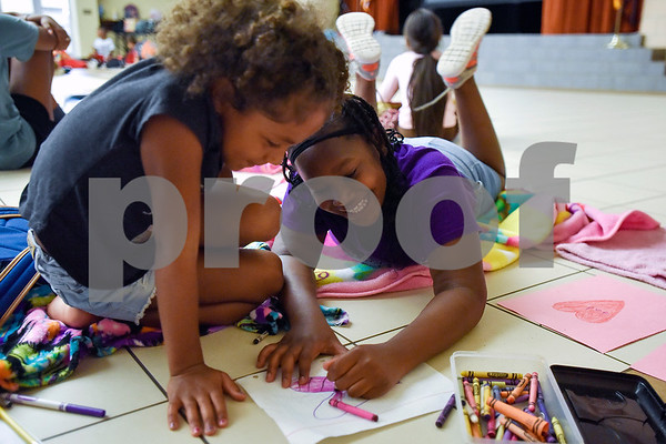 Kilyn, 5, looks at Kaylee Shears', 8, drawing as Shears smiles during Rose City Summer Camps at Dixie Elementary School in Tyler, Texas, on Wednesday, July 19, 2017. Rose City Summer Camps, a ministry of The Mentoring Alliance, is a faith-based and academic summer camp for kids. (Chelsea Purgahn/Tyler Morning Telegraph)