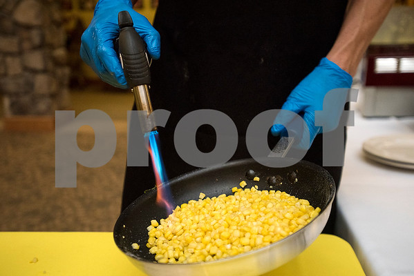 Dustin Chamberlain caramelizes corn for a dessert during the chef showdown at Atria Willow Park in Tyler, Texas, on Thursday, July 20, 2017. Two teams faced off and cooked an appetizer, entree and dessert for judges, with all dishes including corn. (Chelsea Purgahn/Tyler Morning Telegraph)