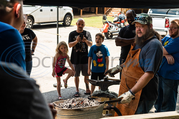 Bladesmith Johnathan Sibley heats up a piece of carbon steel in a coal forge as attendees look on and ask questions during a live forging demonstration Saturday in front of The Blade Bar in downtown Ben Wheeler.  (Cara Campbell/Tyler Morning Telegraph)
