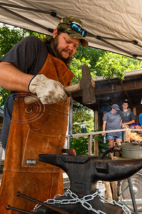 Bladesmith Johnathan Sibley beats down on a long piece of burning hot high carbon steel with a hammer, shaping it into what will be a knife, as attendees looked on during a live forging demonstration Saturday in front of The Blade Bar in downtown Ben Wheeler.  (Cara Campbell/Tyler Morning Telegraph)