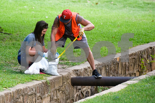 Amanda Folmar holds a bag as Dan Crawford disposes of a piece of trash during a cleanup with South Tyler Rotary members at Bergfeld Park as part of Keep Tyler Beautiful's Adopt-A-Park Program in Tyler, Texas, on Monday, July 30, 2018. (Chelsea Purgahn/Tyler Morning Telegraph)