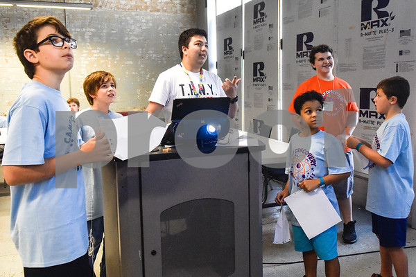 Shawn Fox, center, uses a projector to show campers instructions on how to make a paper airplane during the Take Flight and Make it Move Camp at Discovery Science Place in Tyler, Texas, on Monday, July 30, 2018. (Chelsea Purgahn/Tyler Morning Telegraph)