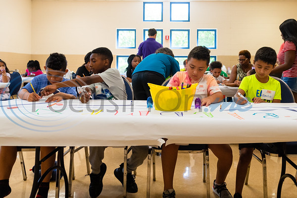 Makhyre Hartsfield (left), Micah Simpson and brothers Julian and Emilio Chavez draw their dream Gassaway Park playground during a kick off event for Tyler Parks and Recreation's KaBOOM! project Tuesday at Glass Recreation Center.   (Cara Campbell/Tyler Morning Telegraph)