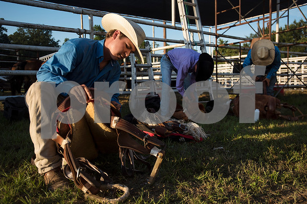 Kevin Boyles, left, preps for the saddle bronc competition during the Mineola Volunteer Fire Department Rodeo at the Fire Department Rodeo Arena in Mineola, Texas, on Friday, July 7, 2017. The rodeo featured a number of rodeo events from barrel racing to steer wrestling. (Chelsea Purgahn/Tyler Morning Telegraph)