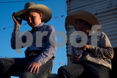 Caden Jordan, 11, adjusts his hat as his friend Cort Gambino, 12, sits behind him during the Mineola Volunteer Fire Department Rodeo at the Fire Department Rodeo Arena in Mineola, Texas, on Friday, July 7, 2017. The rodeo featured a number of rodeo events from barrel racing to steer wrestling. (Chelsea Purgahn/Tyler Morning Telegraph)