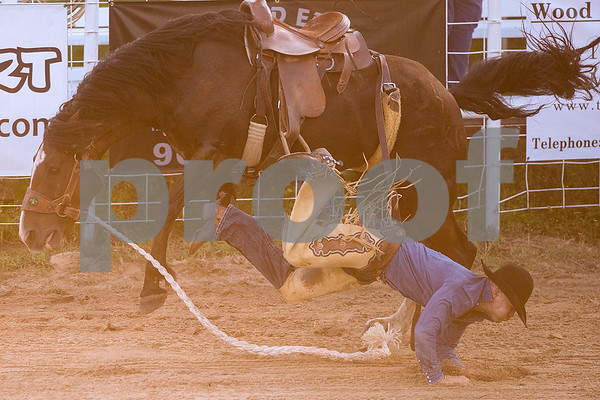 A person falls during the bareback bronc riding competition during the Mineola Volunteer Fire Department Rodeo at the Fire Department Rodeo Arena in Mineola, Texas, on Friday, July 7, 2017. The rodeo featured a number of rodeo events from barrel racing to steer wrestling. (Chelsea Purgahn/Tyler Morning Telegraph)