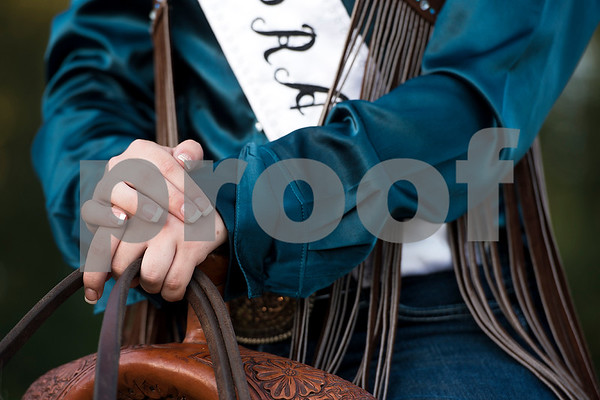 Rebekah McQueen rests her hands on her saddle during the Mineola Volunteer Fire Department Rodeo at the Fire Department Rodeo Arena in Mineola, Texas, on Friday, July 7, 2017. The rodeo featured a number of rodeo events from barrel racing to steer wrestling. (Chelsea Purgahn/Tyler Morning Telegraph)