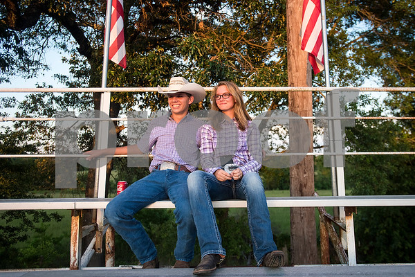 Jake Lee and Kasie Murdock watch the bareback bronc riding during the Mineola Volunteer Fire Department Rodeo at the Fire Department Rodeo Arena in Mineola, Texas, on Friday, July 7, 2017. The rodeo featured a number of rodeo events from barrel racing to steer wrestling. (Chelsea Purgahn/Tyler Morning Telegraph)