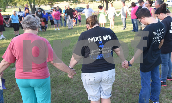 """Jamie Medina of Lindale wears a shirt reading """"police mom"""" at a prayer gathering lead by Chad McElyea, a Lindale Police Department detective, at Pool Park in Lindale Friday. The event was in response to the police officers killed Thursday night in downtown Dallas by a sniper.  (Sarah A. Miller/Tyler Morning Telegraph)"""