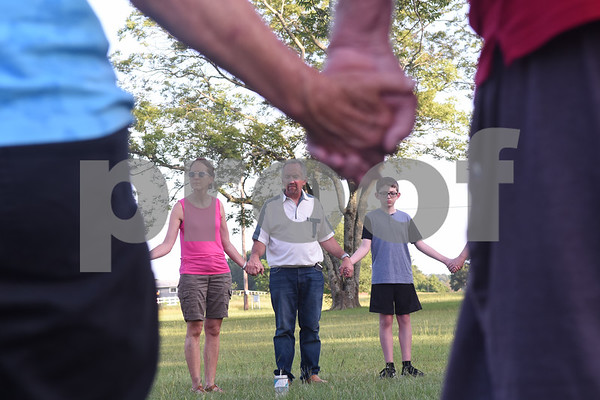 Karen Miller, Tim Miller and Conner Belcher, 13, hold hands at a prayer gathering lead by Chad McElyea, a Lindale Police Department detective, at Pool Park in Lindale Friday. The event was in response to the police officers killed Thursday night in downtown Dallas by a sniper.  (Sarah A. Miller/Tyler Morning Telegraph)