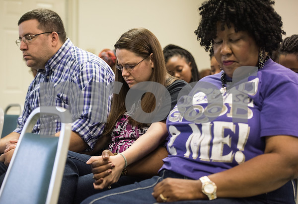 Robert Garcia, Shanna Garcia and Lena Runnels Johnson hold hands at the Together We Stand community event at College Hill Baptist Church in Tyler Saturday July 9, 2016. The town hall style meeting focused on law enforcement, education and race relations. Robert Garcia is a Smith County Crisis Intervention Team Deputy.   (Sarah A. Miller/Tyler Morning Telegraph)