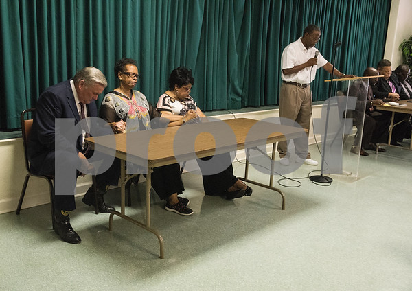 Smith County Sheriff Larry Smith, Rev. Orenthia Mason and Tyler ISD Board of Trustees member Jean Washington bow their heads as Pastor Cleve H. Forward of Whippoorwill Church of the Living God in Henderson leads a prayer at the Together We Stand community event at College Hill Baptist Church in Tyler Saturday July 9, 2016.   (Sarah A. Miller/Tyler Morning Telegraph)