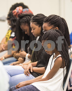 Sasha Smith, 10, bows her head in prayer with her sisters at the Together We Stand community event at College Hill Baptist Church in Tyler Saturday July 9, 2016. The town hall style meeting focused on law enforcement, education and race relations.   (Sarah A. Miller/Tyler Morning Telegraph)
