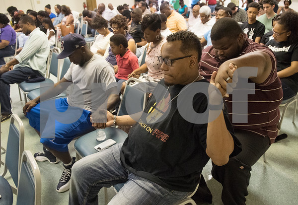 Demarcus Russeau of Born King Mentorship and Pastor Donnell Walder and El-Manuell Allen of Church of Fire, hold hands as they pray during the Together We Stand community event at College Hill Baptist Church in Tyler Saturday July 9, 2016. The town hall style meeting addressed race and law enforcement relations in wake of the Black Lives Matter and Blue Lives Matter movements.  (Sarah A. Miller/Tyler Morning Telegraph)