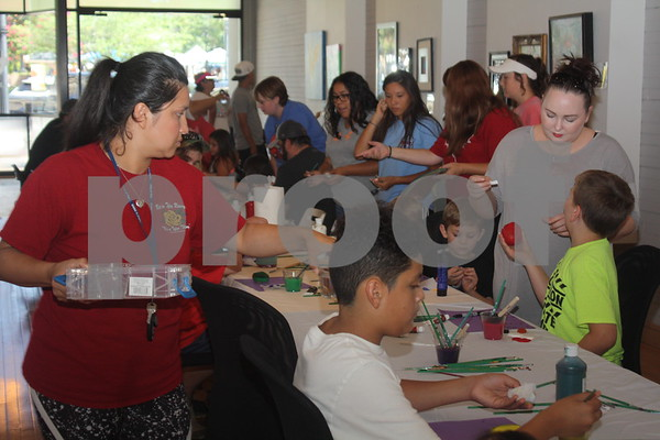 Children of all ages learning to paint rocks at the Gallery Main Street, Downtown Tyler, during Hit The Bricks Art Fair.