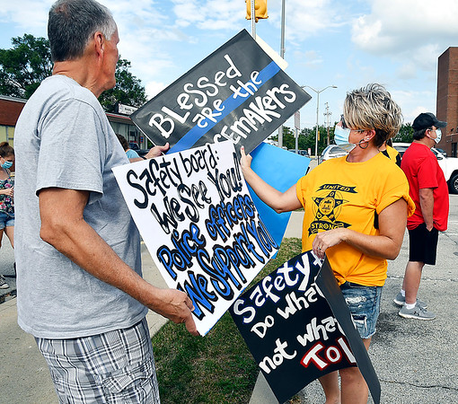 People at the FOP rally look over hand-made signs made by Linda Woschitz she brought to help show her support for the local law enforcement members.