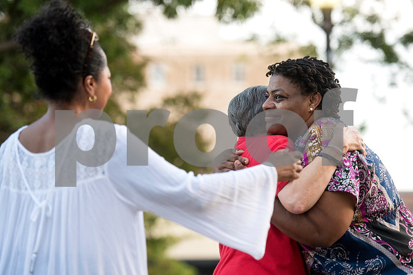 Debbie Kirkland Waffer walks up to give Brenda McWilliams, center, a hug as McWilliams hugs organizer Delia Gray during the Inspiring Peace Rally at T.B. Butler Fountain Plaza in Tyler, Texas, on Thursday, Aug. 17, 2017. Around 75 people attended the rally to discuss ways the community could unify. The rally was held partially in response to the attack in Charlottesville on Aug. 12, where one person was killed and 19 more injured after a car struck a group of counter-protesters demonstrating against a white nationalist rally. (Chelsea Purgahn/Tyler Morning Telegraph)