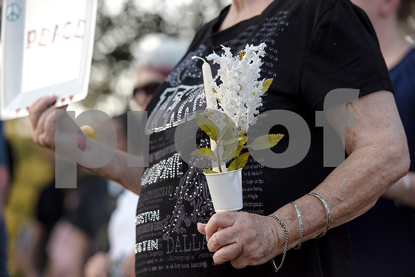 Yvonne Thrash holds a sign, flowers and a candle during the Inspiring Peace Rally at T.B. Butler Fountain Plaza in Tyler, Texas, on Thursday, Aug. 17, 2017. Around 75 people attended the rally to discuss ways the community could unify. The rally was held partially in response to the attack in Charlottesville on Aug. 12, where one person was killed and 19 more injured after a car struck a group of counter-protesters demonstrating against a white nationalist rally. (Chelsea Purgahn/Tyler Morning Telegraph)