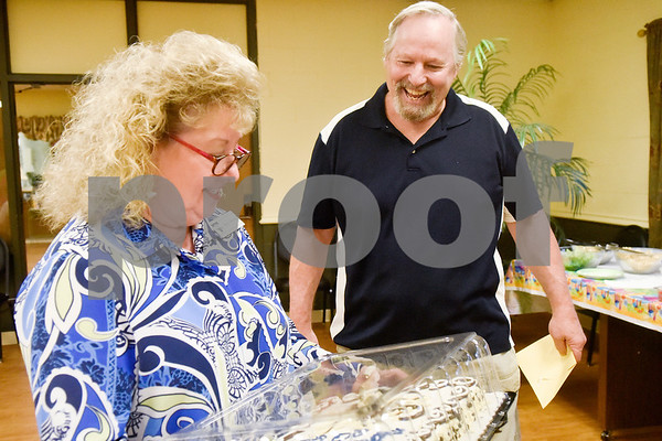 Kay Odom surprises Doug Scroggins with a birthday cake during a painting party at the Tyler Senior Center in Tyler, Texas, on Thursday, Aug. 23, 2018. (Chelsea Purgahn/Tyler Morning Telegraph)