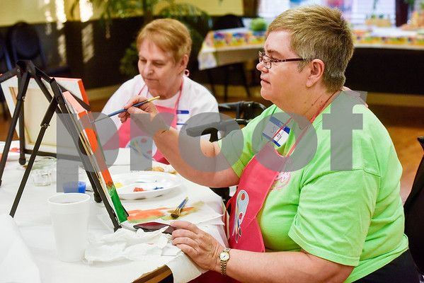 Sandra Rogers and Suzan Burgett paint during a painting party at the Tyler Senior Center in Tyler, Texas, on Thursday, Aug. 23, 2018. (Chelsea Purgahn/Tyler Morning Telegraph)