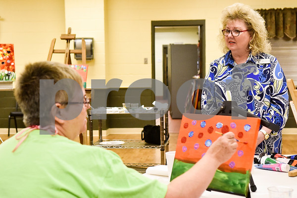 Suzan Burgett paints as Kay Odom talks during a painting party at the Tyler Senior Center in Tyler, Texas, on Thursday, Aug. 23, 2018. (Chelsea Purgahn/Tyler Morning Telegraph)