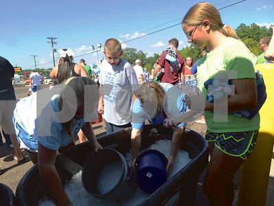 Participants gather ice in their buckets prior to the event. The ice was was donated by the Twice the Ice station. (Victor Texcucano/Staff)