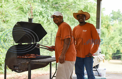 747 Riders Club Vice President Larry Hinton (left) and club member Johnny Propes (right) grill hot dogs at the Pack the Park charity event at Nichols Green Park in Jacksonville on Saturday, August 24. The club hosted the event which offered local children free school supplies, lunch and games. (Jessica T. Payne/Tyler Morning Telegraph)