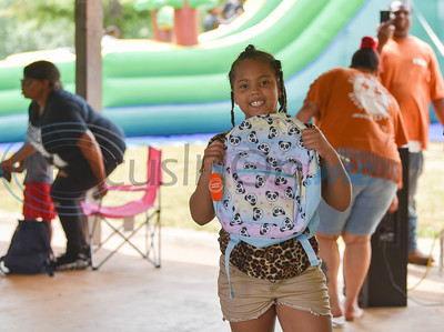 Fred Douglass Elementary student Kynnedi Gipson, 7, holds up a backpack she won at the Pack the Park charity event at Nichols Green Park on Saturday, August 24. The event provided local children with free school supplies, lunch and games. (Jessica T. Payne/Tyler Morning Telegraph)