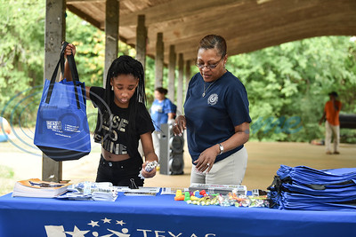 Kimberly Friend (right) of the Texas Department of State Health Services and her granddaughter Aniya Williams (left) stuff bags for local children at the Pack the Park charity event hosted by the 747 Riders Club. The event was held at Nichols Green Park in Jacksonville on Saturday August 24 and provided free school supplies, lunch and games. (Jessica T. Payne/Tyler Morning Telegraph)