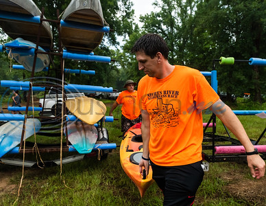 Father and son volunteers Dwayne (back) and Kayne Parrish help distribute kayaks to participants during the 29th annual Neches River Wilderness Race Saturday morning, Aug. 3, 2019, at a starting point in the Lake Palestine dam area on Highway 79 between Jacksonville and Palenstine. The 22-mile river race was put on by the Neches River Runner Paddling Club.  (Cara Campbell/Tyler Morning Telegraph)