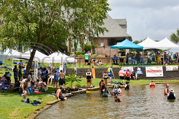 Attendees sit in the shade and wade in the water during the 8th Annual Adaptive Aquafest Saturday on Lake Palestine in Bullard. The event provides wheelchair-bound adults and children access to water sports with the help of professionals.   (Cara Campbell/Tyler Morning Telegraph)