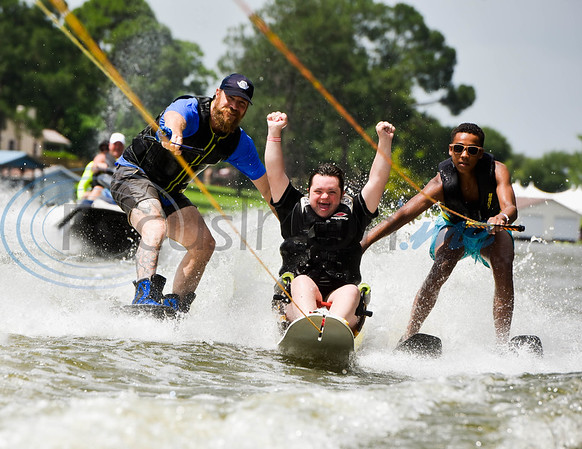 """Griffin Hollowell (center), with a smile and his fists in the air, lets out an excited """"Yeah"""" as he wakeboards across the water with assists from from volunteer skiers Joel Raurk (left) and Jonah Chatelain during the 8th Annual Adaptive Aquafest Saturday on Lake Palestine in Bullard. The event provides wheelchair-bound adults and children access to water sports with the help of professionals.   (Cara Campbell/Tyler Morning Telegraph)"""