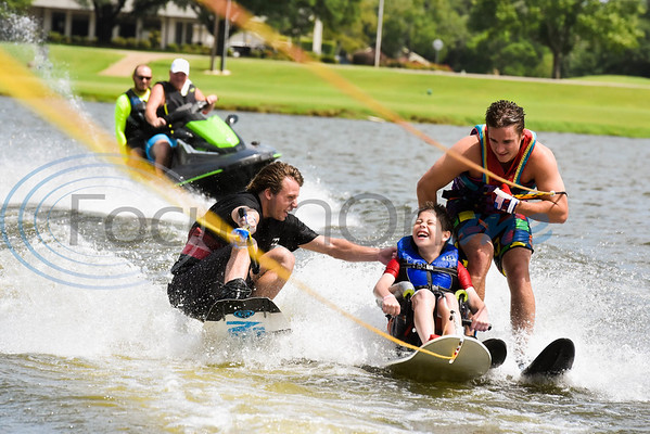 Logan Hollowell (center) flashes a smile as he wakeboards with help from from Texas Adaptive Aquatics volunteers Logan Crouch (left) and Jackson Driggs during the 8th Annual Adaptive Aquafest Saturday on Lake Palestine in Bullard. The event provides wheelchair-bound adults and children access to water sports with the help of professionals.   (Cara Campbell/Tyler Morning Telegraph)