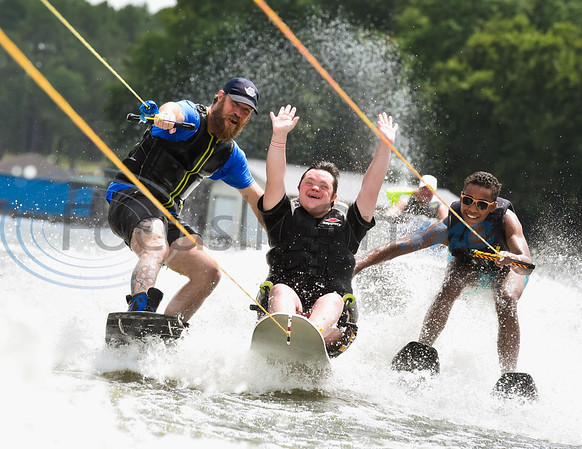 """Griffin Hollowell (center), with a smile and his fists in the air, lets out a loud """"Woohoo"""" as he wakeboards across the water with assists from from volunteer skiers Joel Raurk (left) and Jonah Chatelain during the 8th Annual Adaptive Aquafest Saturday on Lake Palestine in Bullard. The event provides wheelchair-bound adults and children access to water sports with the help of professionals.   (Cara Campbell/Tyler Morning Telegraph)"""