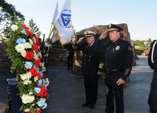 Fire Chief Joe Bruce and Police Chief Tom Deland salute after laying a wreath during the ceremony at the 9/11 Memorial in Community Park in Broomfield on Friday.<br /> <br /> Sept. 11, 2009<br /> Staff photo/David R. Jennings
