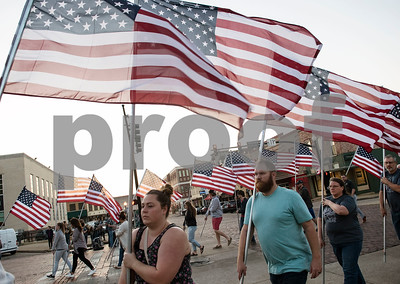 People carry United States flags downtown for a program at T.B. Butler Fountain Plaza in Tyler Monday Sept. 11, 2017 to commemorate the terrorist attacks on Sept. 11, 2001.   (Sarah A. Miller/Tyler Morning Telegraph)