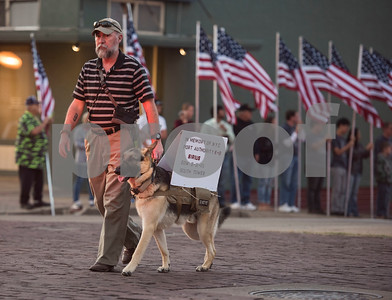 Michael Roark walks with a dog and a sign honoring Sirius, a K-9 officer who was killed on 9/1, during a program at T.B. Butler Fountain Plaza in downtown Tyler Monday Sept. 11, 2017 to commemorate the terrorist attacks on Sept. 11, 2001.   (Sarah A. Miller/Tyler Morning Telegraph)