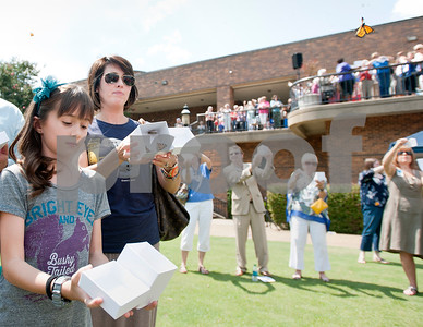 photo by Sarah A. Miller/Tyler Morning Telegraph  Tyler residents Caraline Coker, 9, and her mother Leslie Coker release two boxes of butterflies at the Alzheimer's Alliance's butterfly release event at the Tyler Rose Garden Thursday.  The public was invited to make a donation of 25 dollars each per butterfly.  Over 1,100 butterflies were released to honor and commemorate lives touched by Alzheimer's disease and other dementias in Smith County.